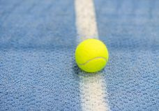 Tennis ball indoor on tennis court, white line. Blue surface, copy space royalty free stock photos