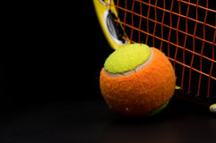 Tennis ball for kids with tennis racket. With green grip handle and orange strings on black background stock images