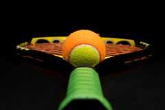 Tennis ball for kids with tennis racket. With green grip handle and orange strings on black background royalty free stock image