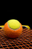 Tennis ball for kids with tennis racket. With green grip handle and orange strings on black background stock photos