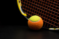 Tennis ball for kids with tennis racket. With green grip handle and orange strings on black background royalty free stock photo