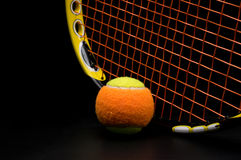 Tennis ball for kids with tennis racket. With green grip handle and orange strings on black background stock photo