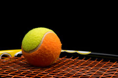 Tennis ball for kids with tennis racket. With green grip handle and orange strings on black background royalty free stock photography