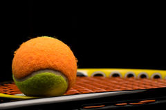 Tennis ball for kids with tennis racket. With green grip handle and orange strings on black background royalty free stock images