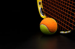 Tennis ball for kids with tennis racket. With green grip handle and orange strings on black background royalty free stock photos
