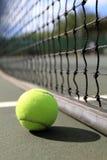 Tennis ball lies next to the net. A tennis ball lies on the court next to the net in the daytime Stock Photos