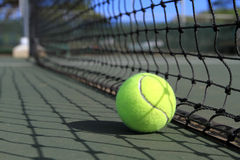 Tennis ball lies next to a net on the court Stock Photography