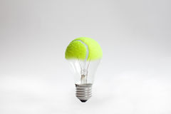 Tennis ball light bulb. Green tennis ball forming part of light bulb, white studio background Stock Image