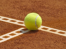 Tennis ball on the line. Detail of clay court with tennis ball on the line stock photography