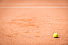 Tennis ball lying in orange sand Royalty Free Stock Photography