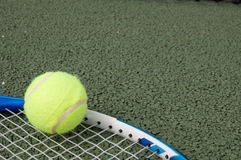Tennis ball. Lying on racquet on tennis court Stock Image