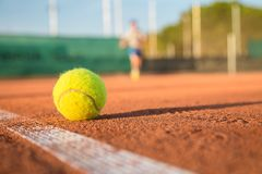 Tennis ball on white line on a sunny day. Tennis ball lying on white line on tennis court on sunny day Royalty Free Stock Image