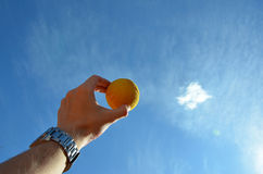 Tennis ball in a man hand showing to the sky Stock Images