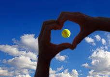 Tennis ball midair with cloudy sky above. View of tennis ball midair with cloudy sky above Stock Photography
