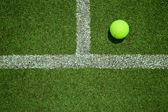 Tennis ball near the line on tennis grass court from top view. G Royalty Free Stock Images