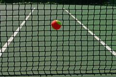Tennis ball in the net. Yellow-red balls on a green tennis court Stock Image