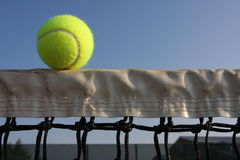 Tennis ball on the net Stock Photography