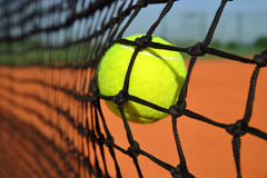 Tennis ball in the net. Tennis ball in the net at a clay court Royalty Free Stock Photos