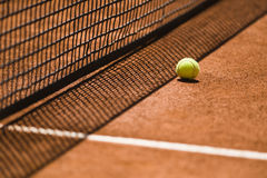 Tennis Ball and Net on a Clay Court Royalty Free Stock Images