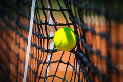 Tennis ball in net Royalty Free Stock Images