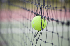 Tennis ball in net at tennis court Stock Images