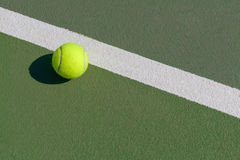 Tennis ball next to line on hard court Royalty Free Stock Photos