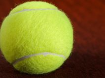 Tennis ball on the orange surface Stock Image