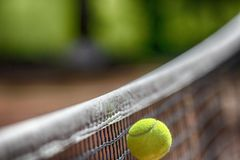 Tennis ball net. Tennis ball over net falls in the opponent field while playing game Royalty Free Stock Photos