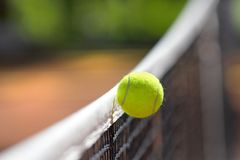 Tennis ball. Over net falls in the opponent field while playing game Royalty Free Stock Photos