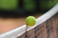Tennis ball over net falls in the opponent's field Stock Photos