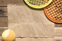 Tennis ball and paper on wood background. Royalty Free Stock Photo