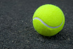 Tennis ball on pavement Royalty Free Stock Photos