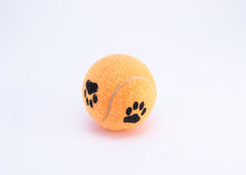 Tennis ball with paws on it. Orange tennis ball with dog paws on it, isolated on white background Royalty Free Stock Photography