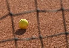 Tennis ball photo through blurred tennis net. Photography stock image