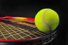 Tennis ball and racket. On black background ready for your type Stock Images