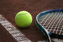 Tennis ball and a racket. On the court ground Royalty Free Stock Image