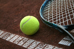 Tennis ball and a racket. On the court ground Royalty Free Stock Photography
