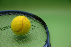 Tennis ball and racket. On green background Royalty Free Stock Images