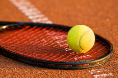 Tennis ball and racket. On the court ground Royalty Free Stock Image