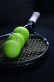 Tennis ball in the racket. On the black background Stock Image