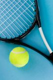 Tennis ball with racket. Tennis ball and racket on blue background Royalty Free Stock Images
