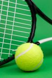 Tennis ball with racket. Tennis ball and racket on green background Stock Image