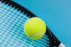 Tennis ball with racket. Tennis ball and racket on blue background Stock Photo
