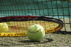 Tennis ball and racket. Background of tennis ball and racket in front of net Stock Photo