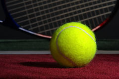 Tennis Ball and Racket on a Court. Tennis ball and racket on soft indoor court surface Stock Photography