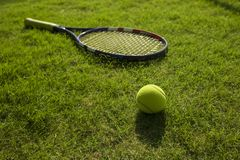 Tennis ball and racket on green grass field ground.  Royalty Free Stock Photos