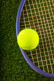 Tennis ball and racket over grass Royalty Free Stock Photo
