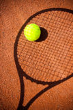 Tennis ball with racket shadow Stock Image