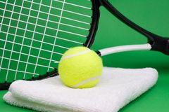 Tennis ball with racket and towel. Tennis ball, racket and towel on green background Stock Photo