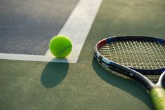 Tennis ball and racket under late evening sunlight.  stock photos